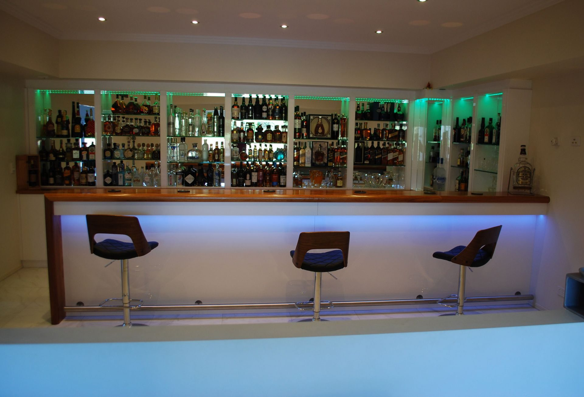 arge bar with wooden counter with white counter and glass shelves