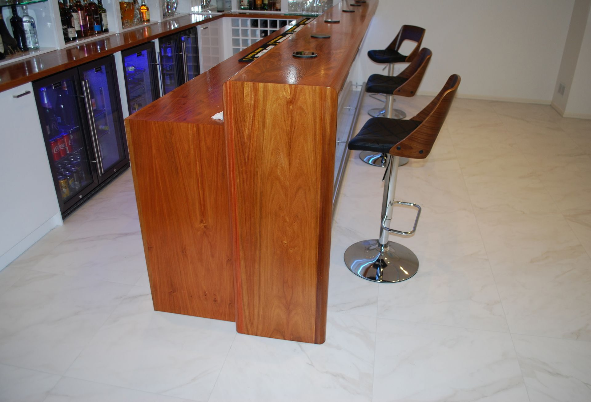 Wooden bar counter with white wall unit