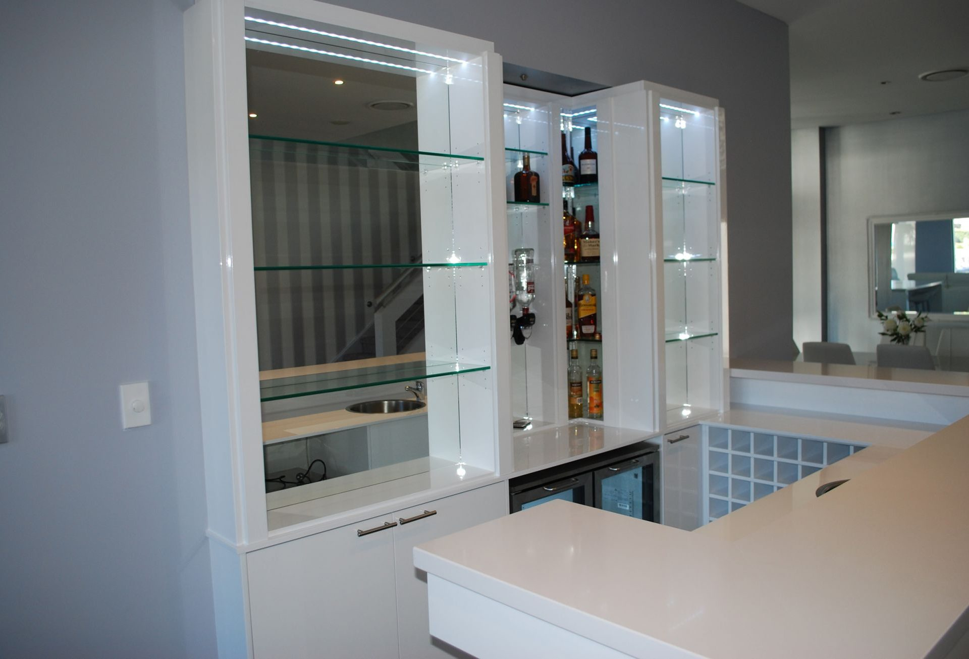 White home bar unit with shelving and dispensers