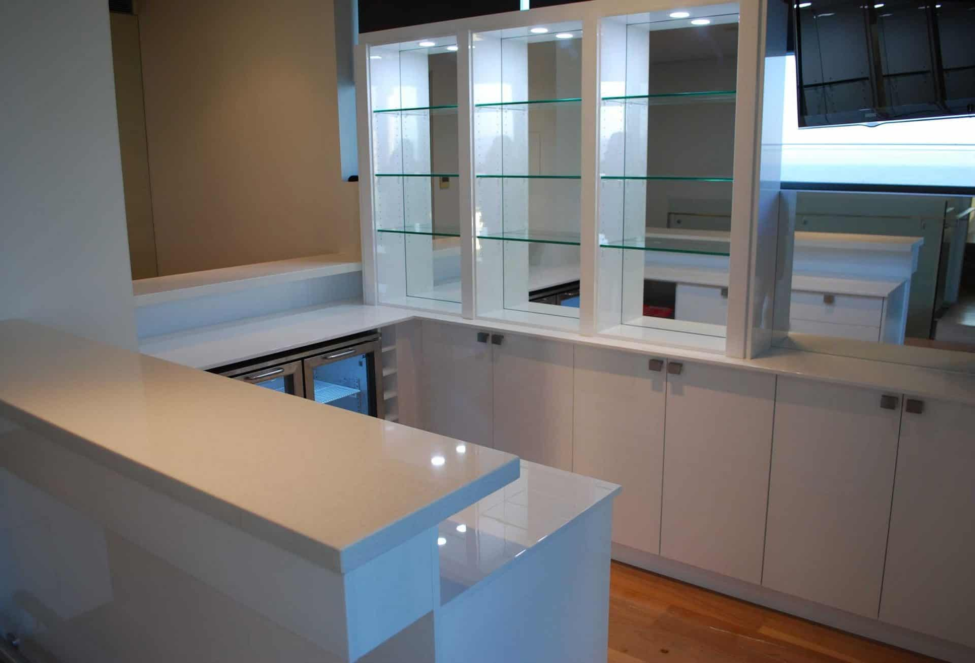 A beautiful example of a custom built home bar with white counter tops and cupboard space and glass shelving with mirror backing and a bar fridge under the counter. Matching the house perfectly.